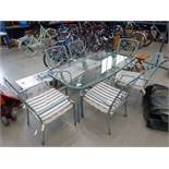 Oval glass topped table on green metal supports with 6 matching chairs and cushions