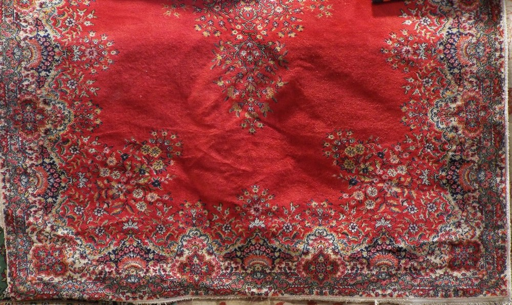 Axminster type carpet decorated with a central floral medallion upon a red ground, 280 x 200 cm
