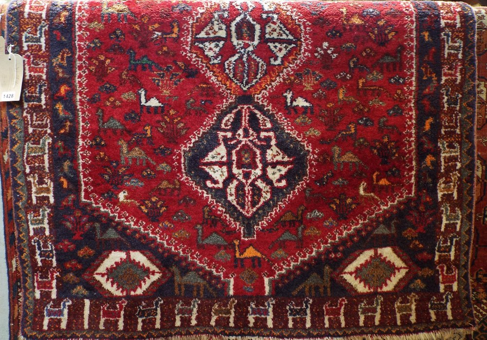 Afghan full pile rug decorated with three central medallions, framed by animal symbols and foliage
