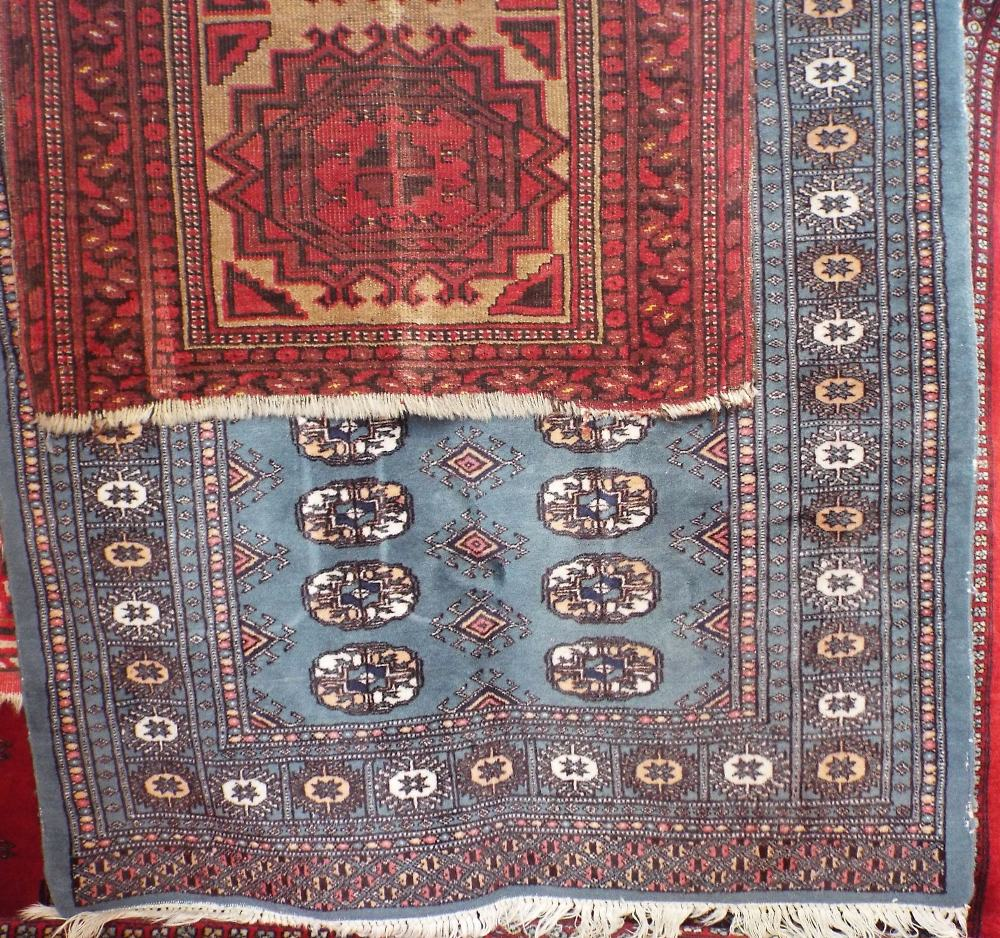 Lot 1442 - Bokhara rug with typical geometric medallions upon a blue ground, 160 x 90 cm; together with an