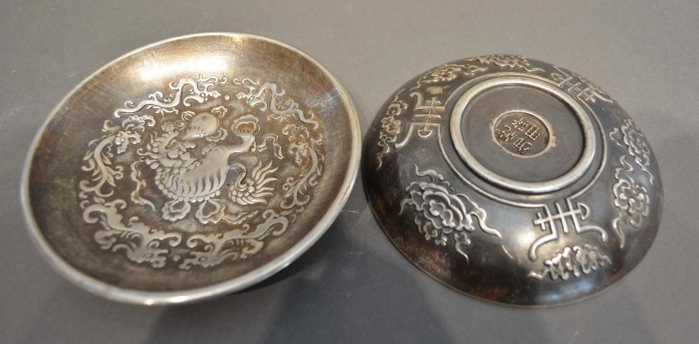 A Pair of Chinese White Metal Bowls decorated in relief with serpents amongst foliage, seal marks to
