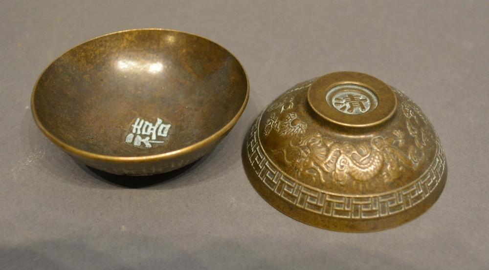 A Pair of Chinese Patinated Bronze Small Bowls decorated in relief with serpents amongst foliage,