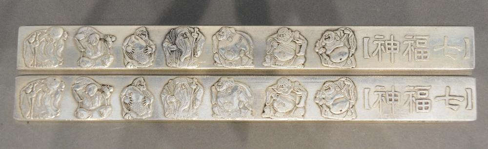 Lot 282 - A Pair of Chinese White Metal Scroll Weights decorated in relief with figures, 23 x 2.5cm