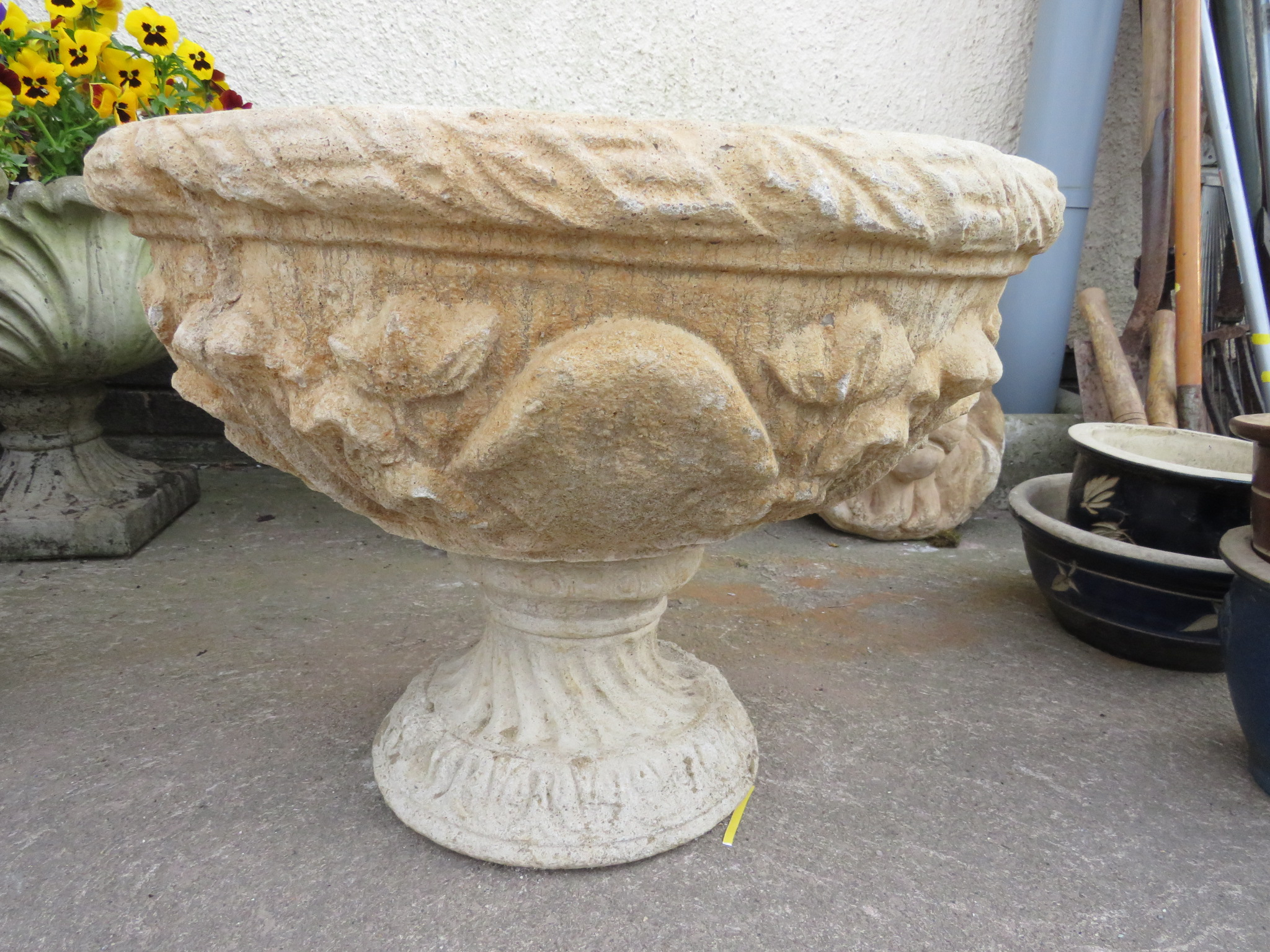 Lot 4 - PAIR OF COMPOSITE STONE URNS ON PLINTHS DECORATED WITH ACANTHUS LEAVES