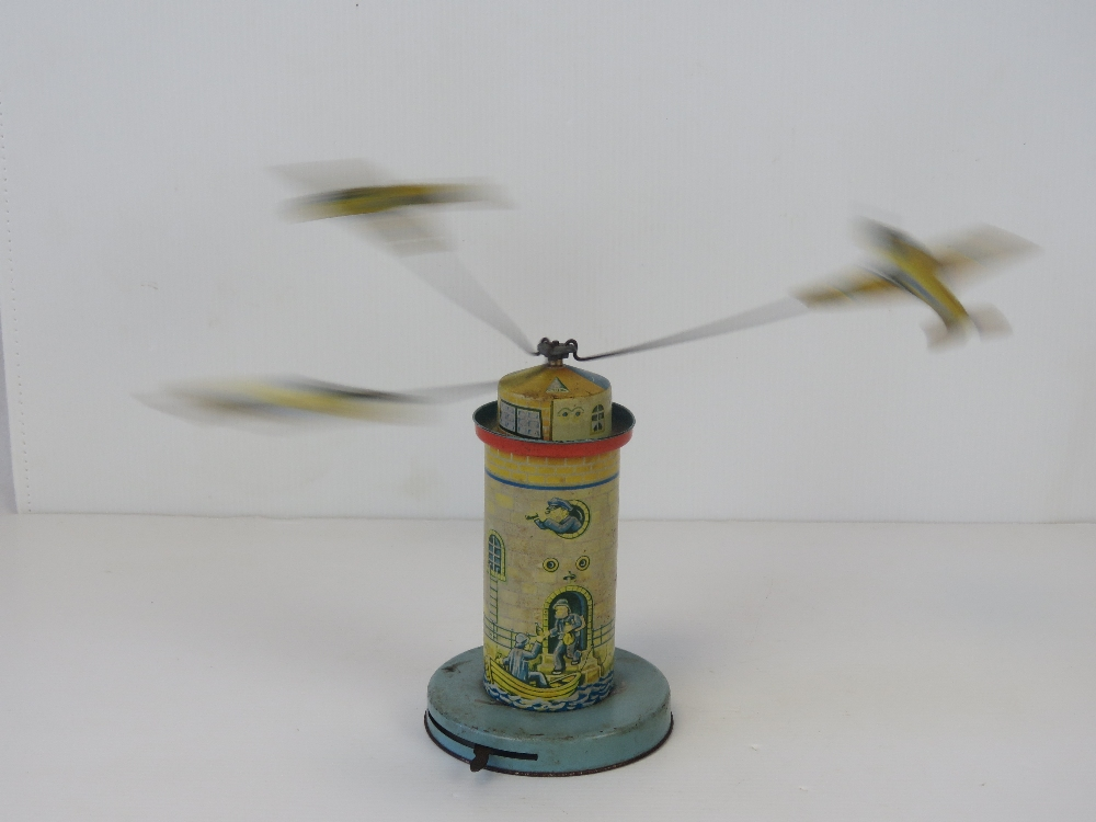 Lot 430 - A vintage tin plate aircraft carousel, standing 15cm high, two aircraft propellers deficient.