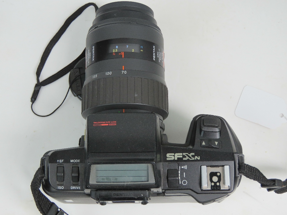 Lot 40 - A Pentax SFX 35mm SLR camera having 70-210mm 1:4-5.6 Pentax lense, with padded carry case.