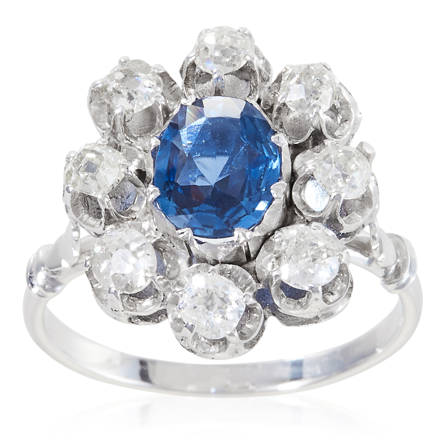 A SAPPHIRE AND DIAMOND CLUSTER RING in platinum or white gold, the oval cut sapphire encircled by