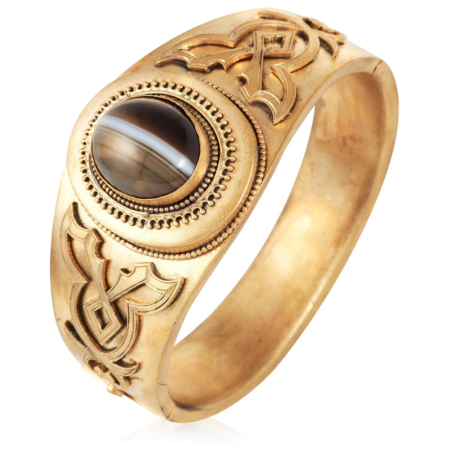 AN ANTIQUE BANDED AGATE BANGLE in yellow gold, set with a cabochon banded agate in scrolling design,