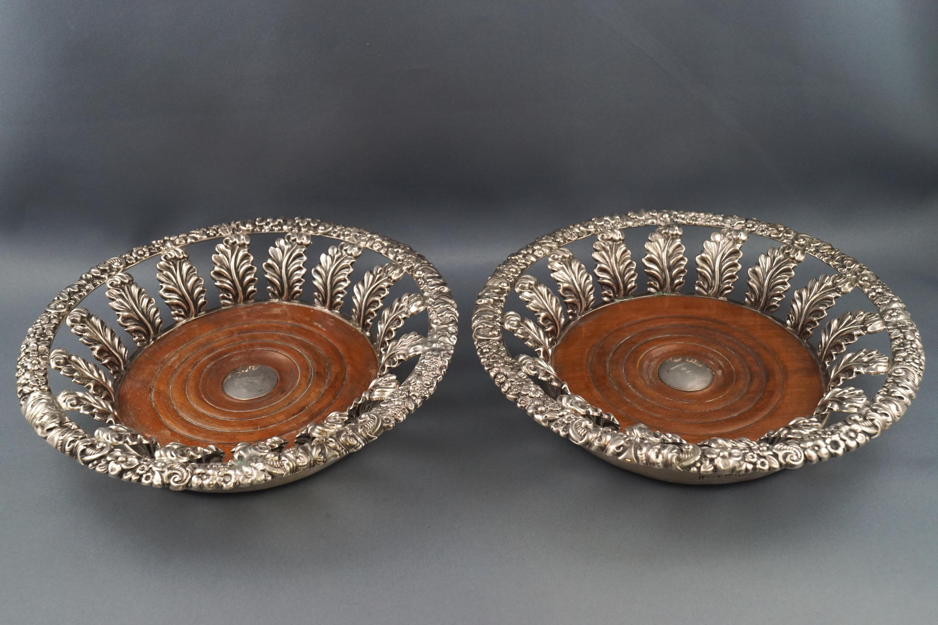 Lot 12 - A pair of George III silver coasters with cast flower head and scrolling foliate rims supported by
