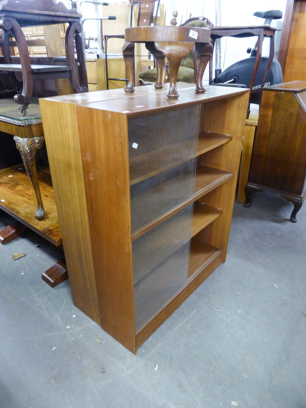 Lot 30 - A SET OF THREE TEAK BOOKCASES, ALL WITH GLASS SLIDING DOORS, ENCLOSING THREE SHELVES (3)