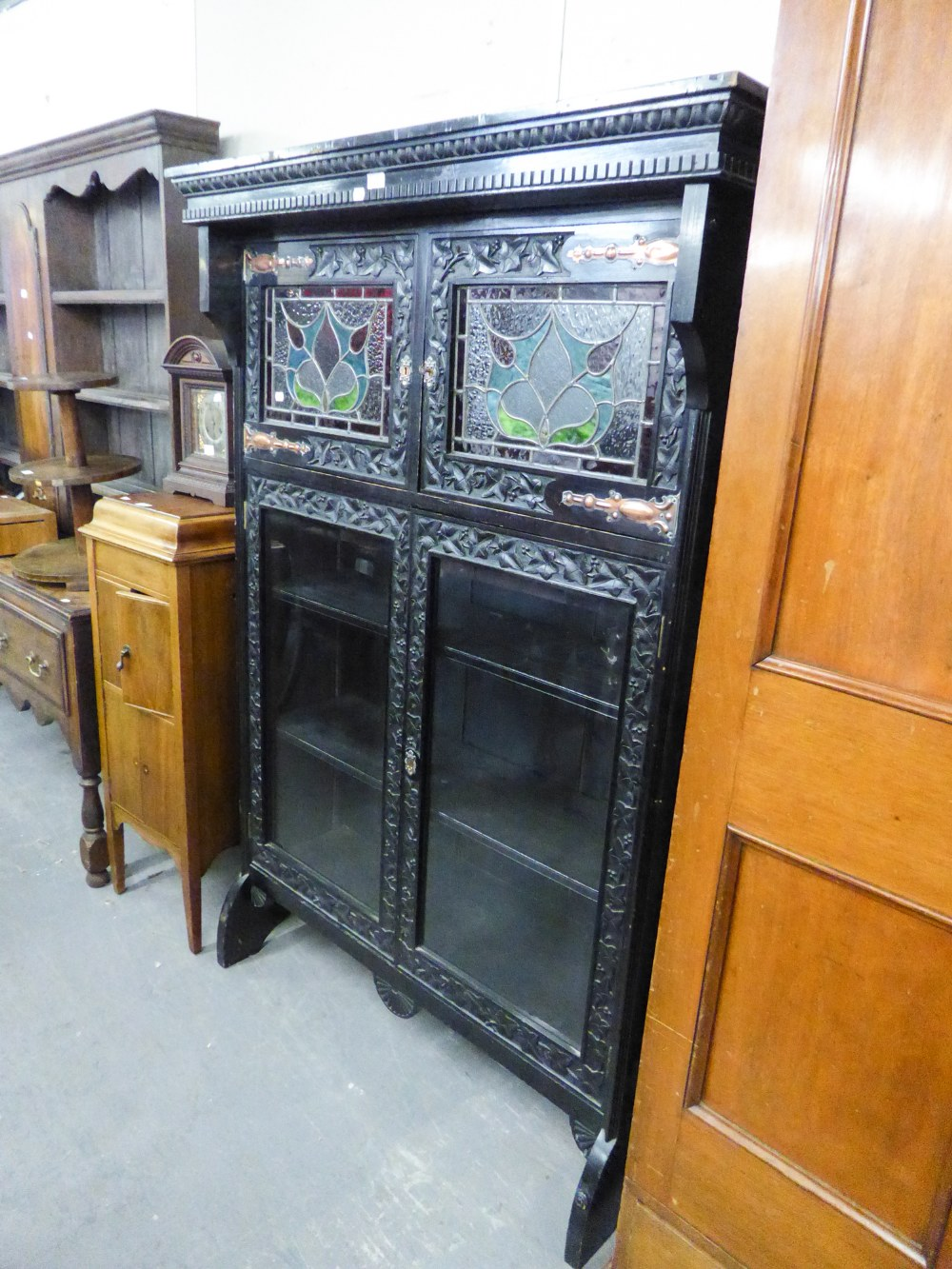 Lot 48 - A LATE NINETEENTH CENTURY DARK OAK BOOKCASE, THE UPPER SECTION ENCLOSED BY TWO LEADED AND STAINED