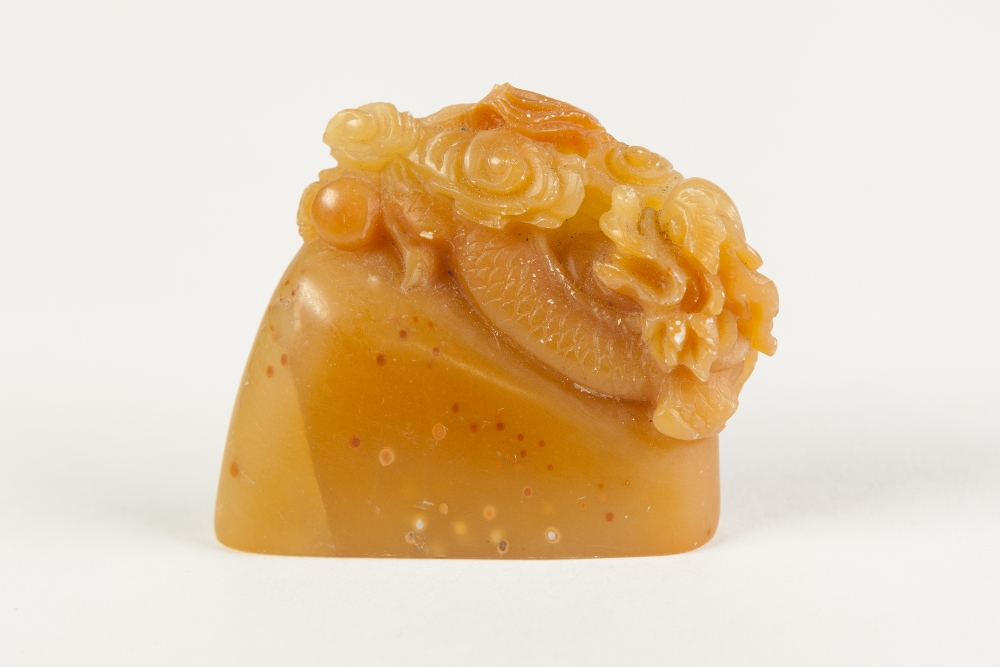 Lot 378 - A CHINESE BROWN HARDSTONE SEAL of flattened section carved with a dragon, issuing from cloud