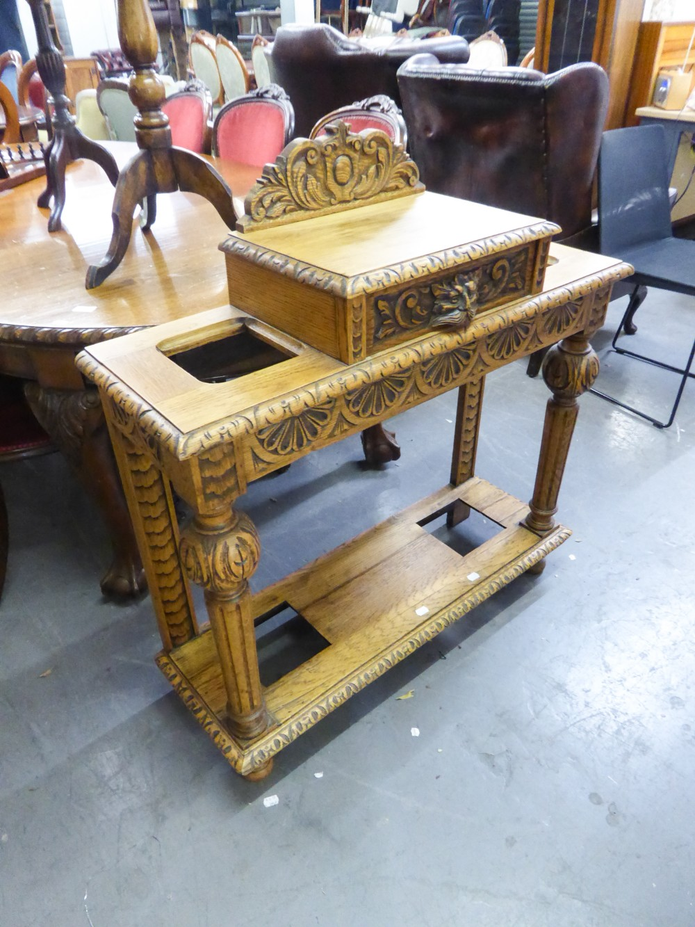 Lot 39 - A 20TH CENTURY OAK HALL STAND WITH RAISED CENTRAL DRAWER HAVING LION HANDLE, UMBRELLA STANDS TO