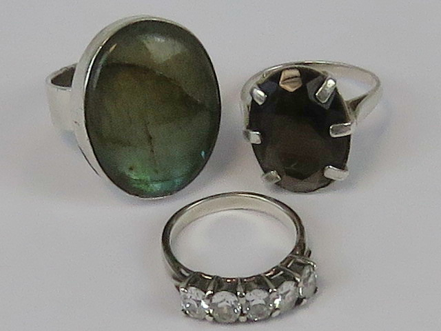 Three silver rings; abalone shell size O