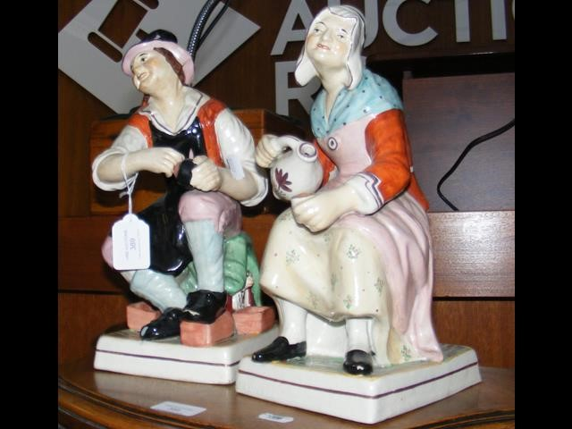 Lot 389 - A pair of Staffordshire style male and female figu