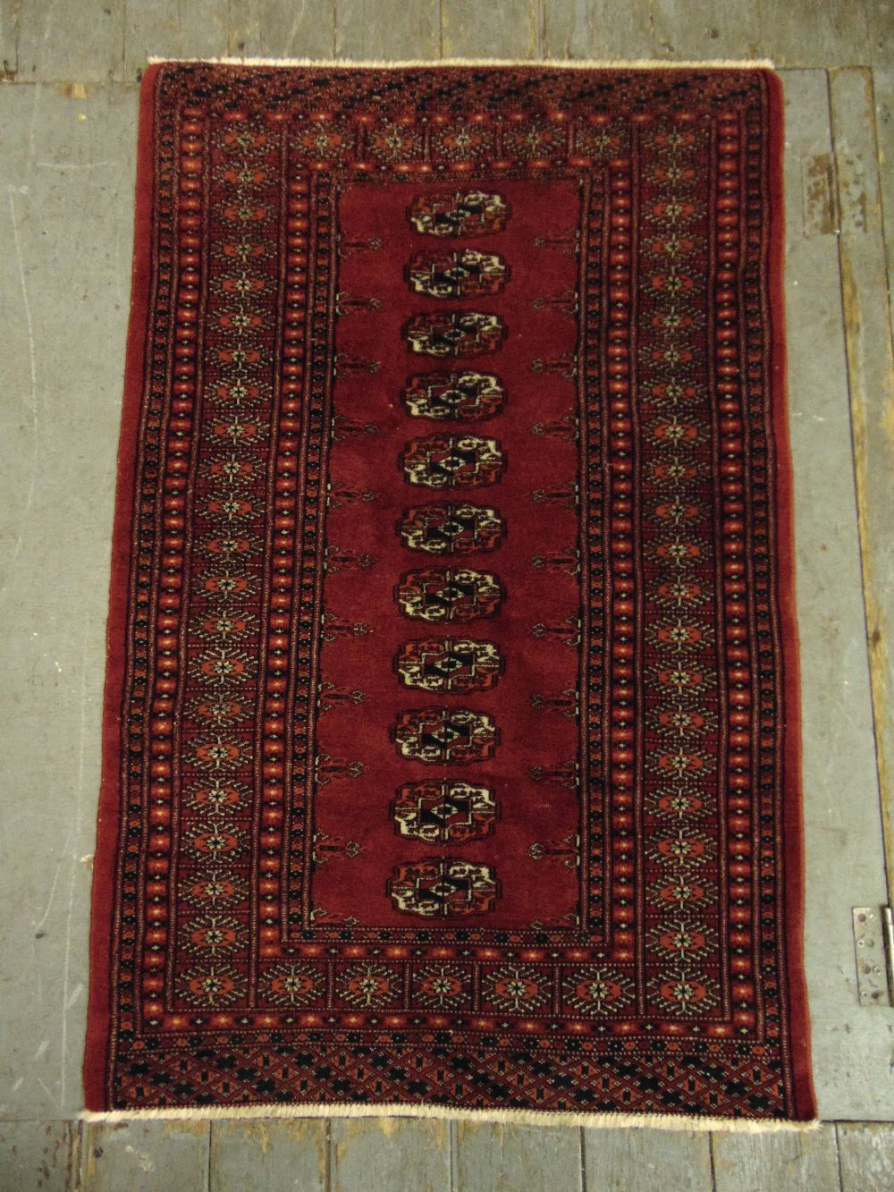 Lot 38 - A Persian wool carpet red ground with repeating geometric pattern and border, 121 x 79cm