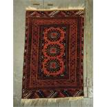 Persian wool carpet red and orange ground with repeating geometric pattern and border, 107 x 73cm