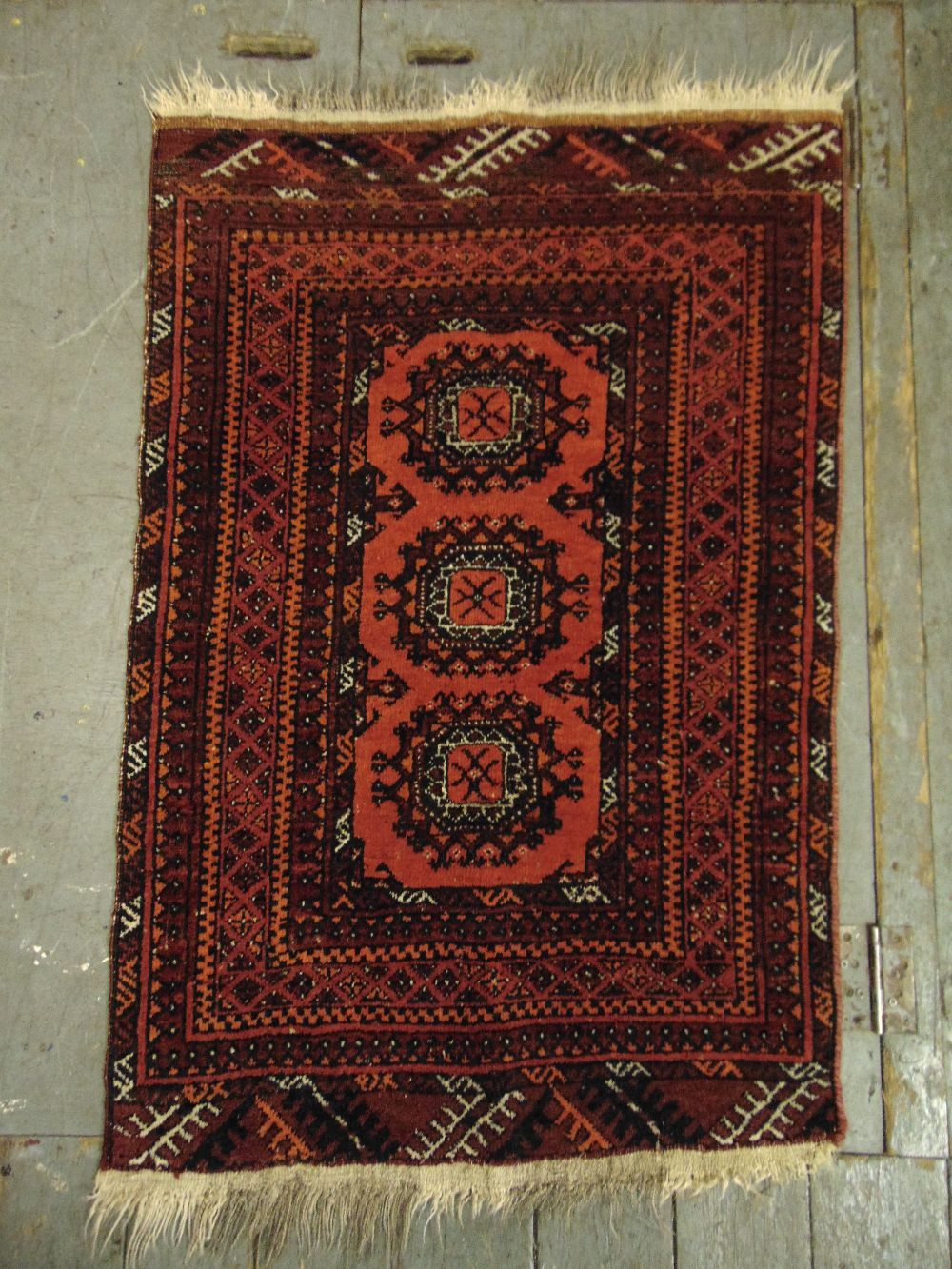 Lot 33 - Persian wool carpet red and orange ground with repeating geometric pattern and border, 107 x 73cm