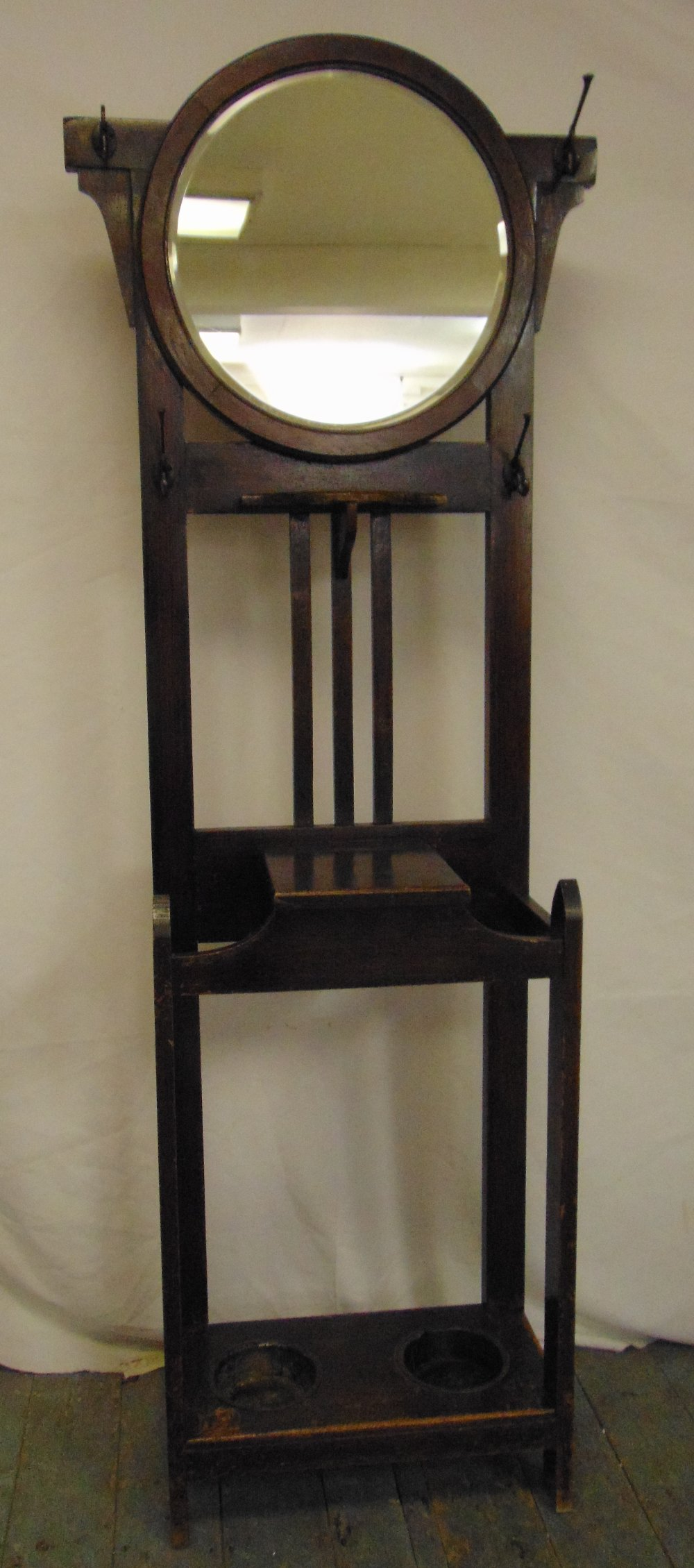 Lot 22 - A Victorian oak hall hat stand in arts and crafts form with oval mirror and integrated umbrella
