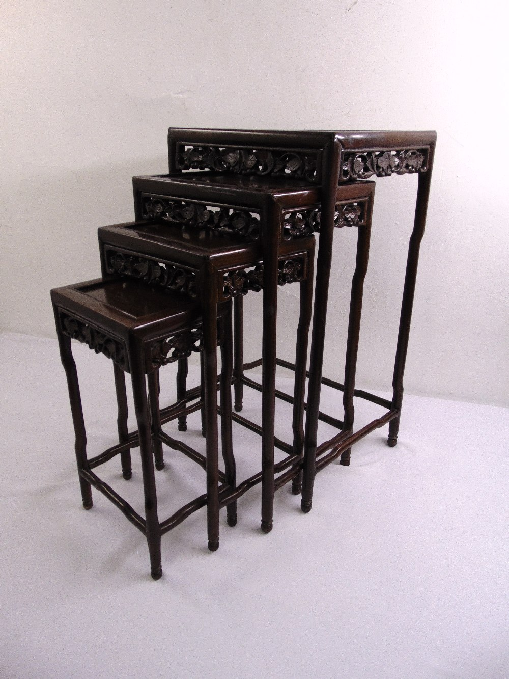Lot 16 - A 20th century quartetto of Chinese hardwood nesting tables, each of rectangular form with foliate