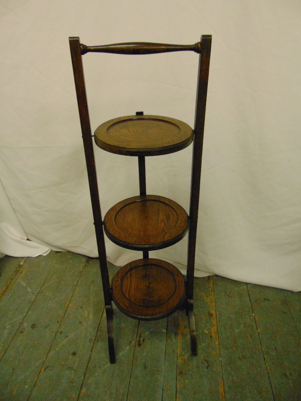 Lot 21 - An oak three tier plate stand of customary form