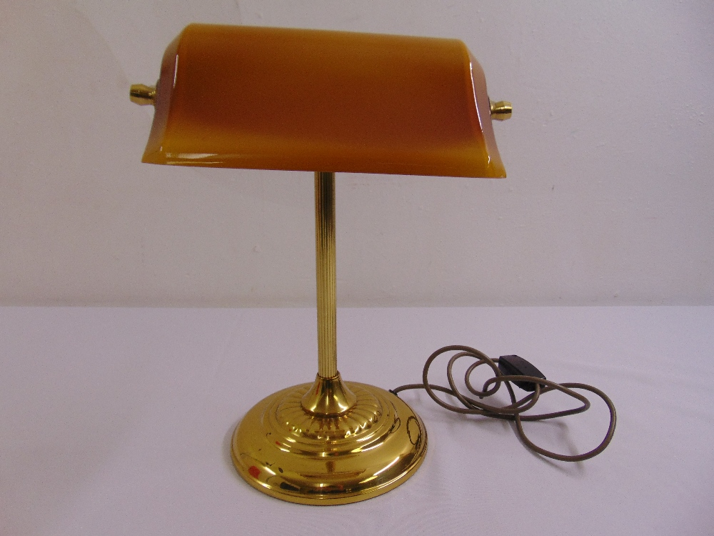 Lot 46 - A brass desk lamp on raised circular base with integrated glass shade