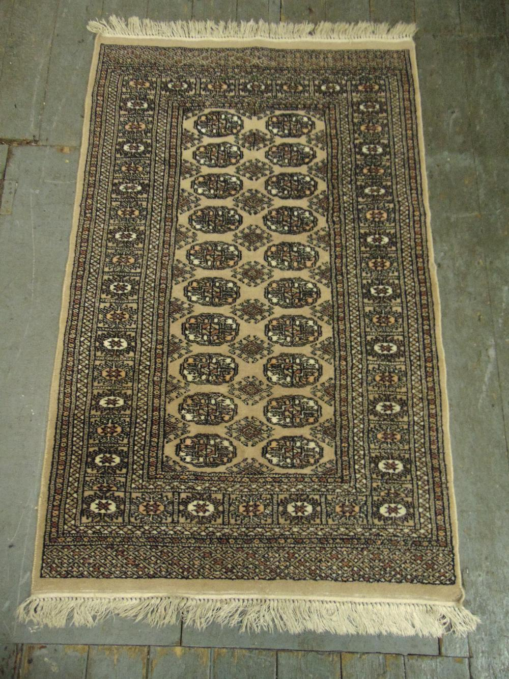 Lot 37 - A Persian wool carpet tan ground with repeating geometric pattern and border, 150 x 95cm