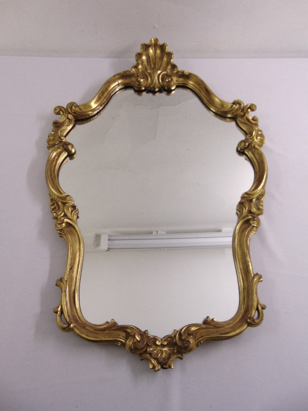 Lot 40 - A shaped oval gilded wooden Rococo style wall mirror