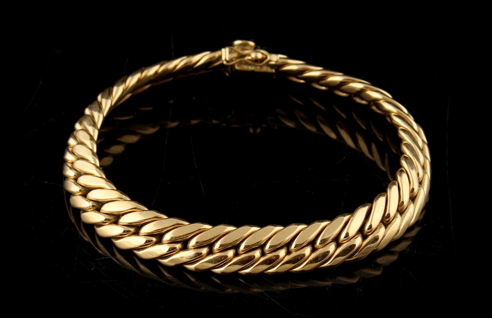 Property of a lady - an 18ct yellow gold flat curb link bracelet, 7.75ins. (19.7cms.) long.