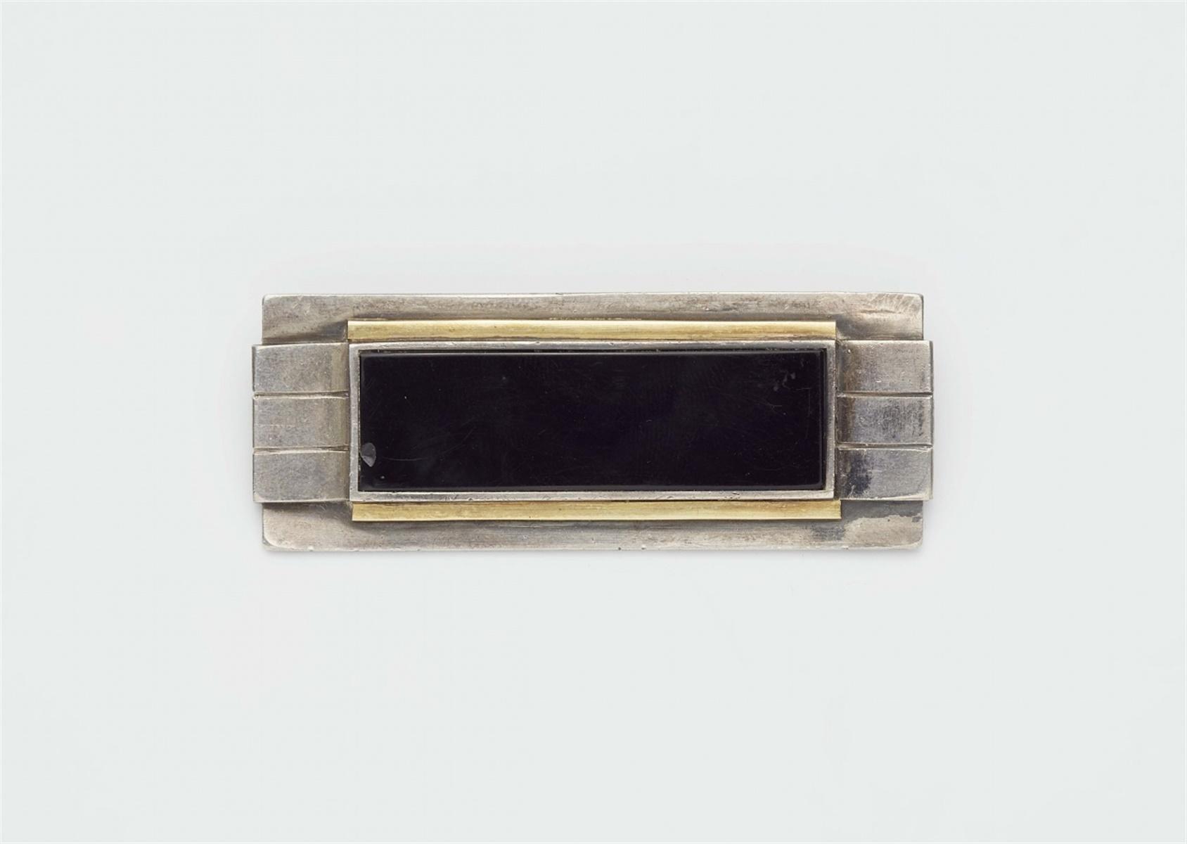 Lot 118 - Brosche von Jean DesprésSilber, Vermeil, wohl Onyx. Oblonge Scheibenform in geometrischer