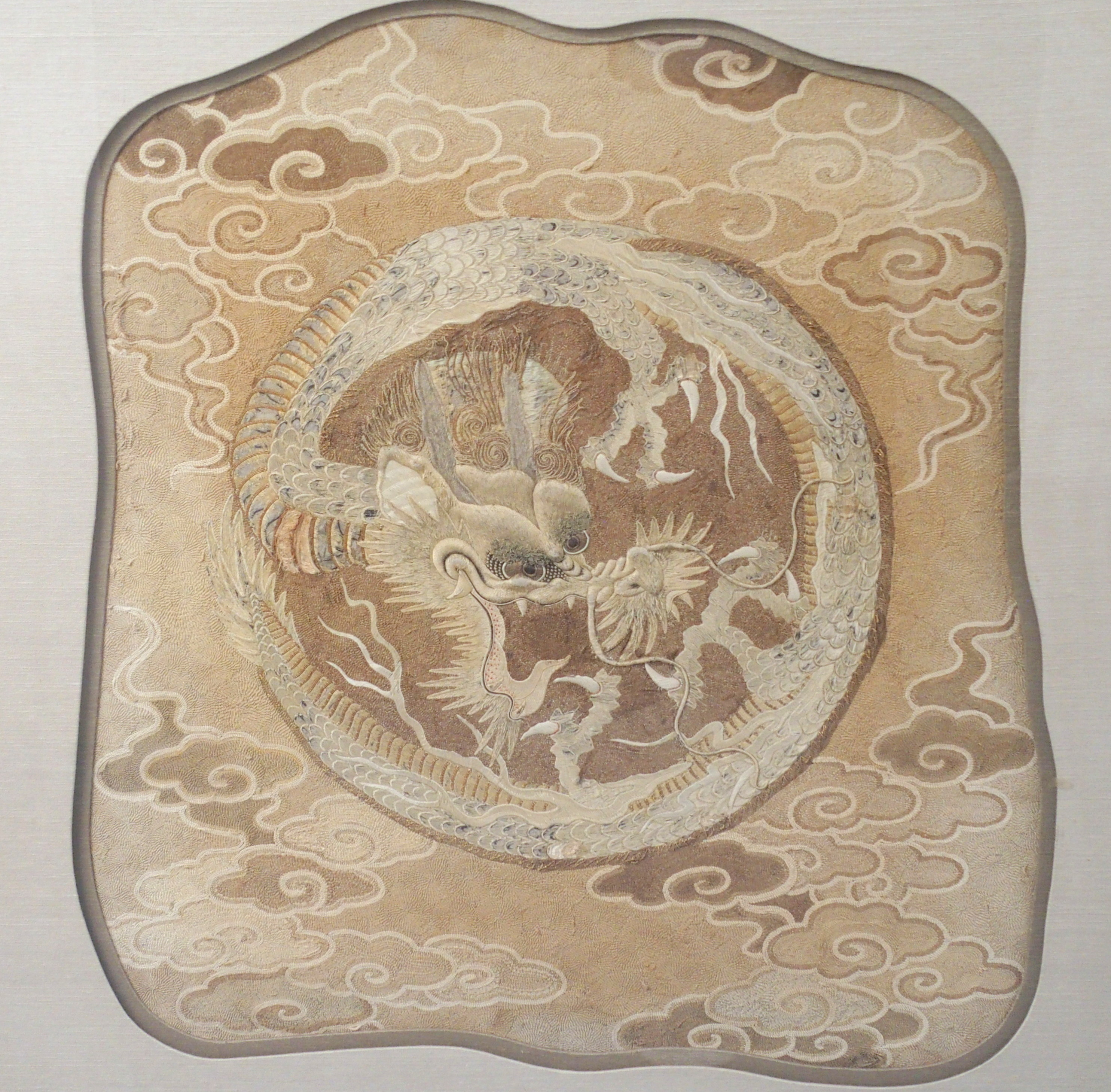 Lot 35 - A CHINESE SILK AND METAL THREAD WOVEN PANEL decorated with a central dragon amongst cloud scrolls,