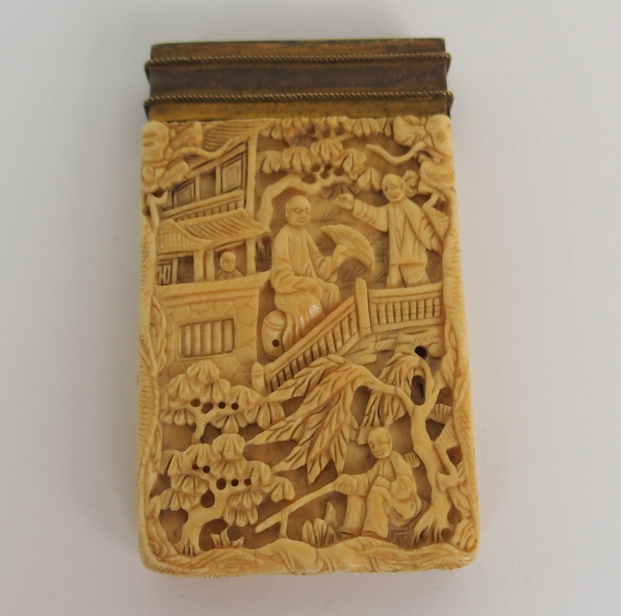 Lot 61 - A CHINESE IVORY CARD CASE carved all over with figures amongst balconies and trees, later brass