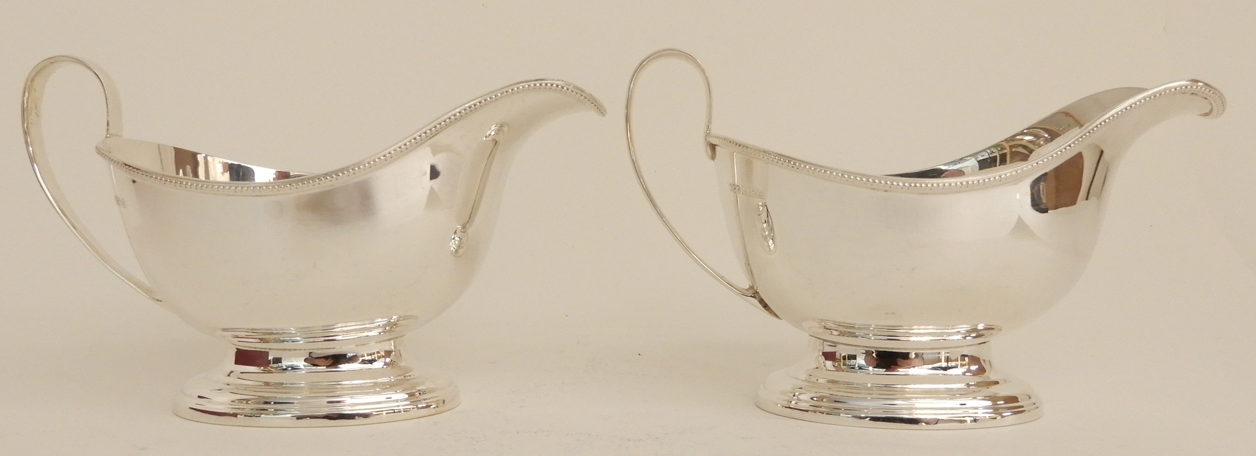 Lot 166 - A CASED PAIR OF SILVER SAUCEBOATS by Henry Clifford Davis, Birmingham 1963, of classic plain shape