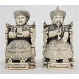 A PAIR OF CHINESE CARVED IVORY EMPEROR AND CONSORT each seated on a throne chair and wearing