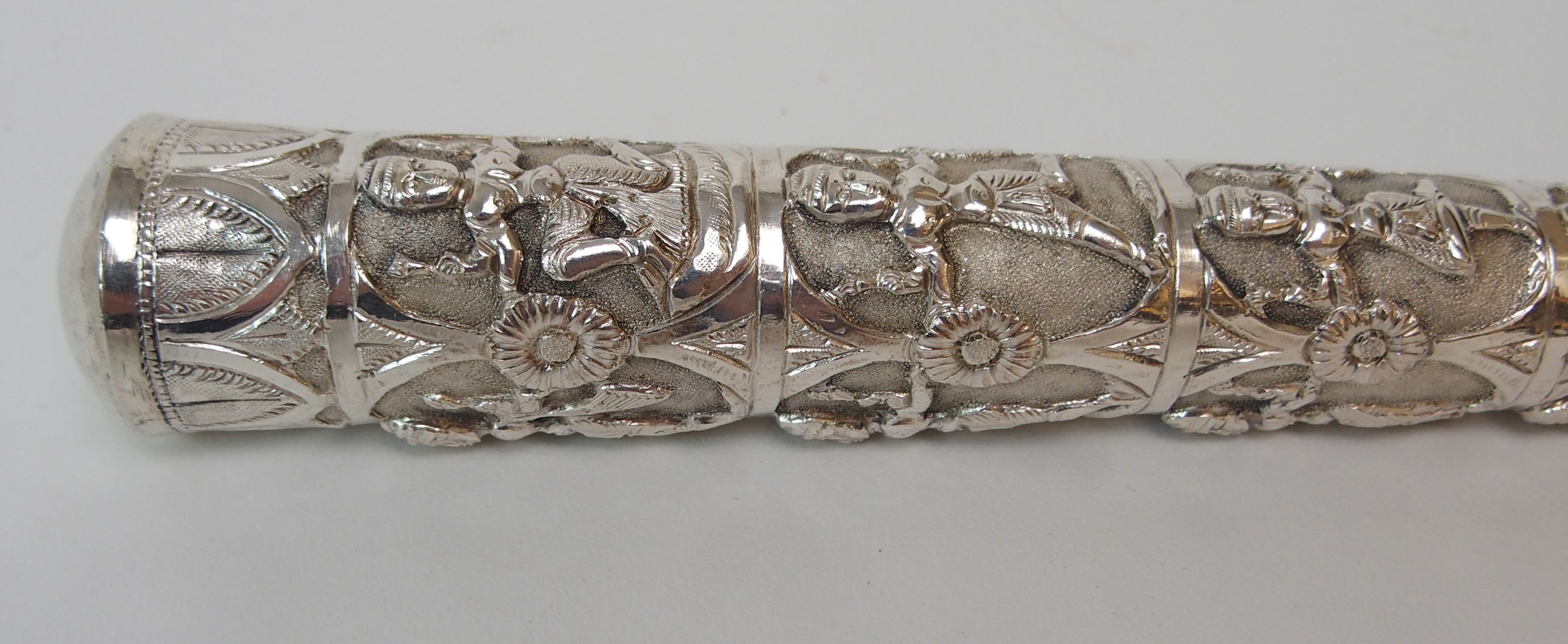 Lot 57 - A BURMESE WHITE METAL PARASOL HANDLE decorated with rows of figures divided by flower head, 122