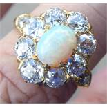 A gold coloured metal ring, set with an opal,