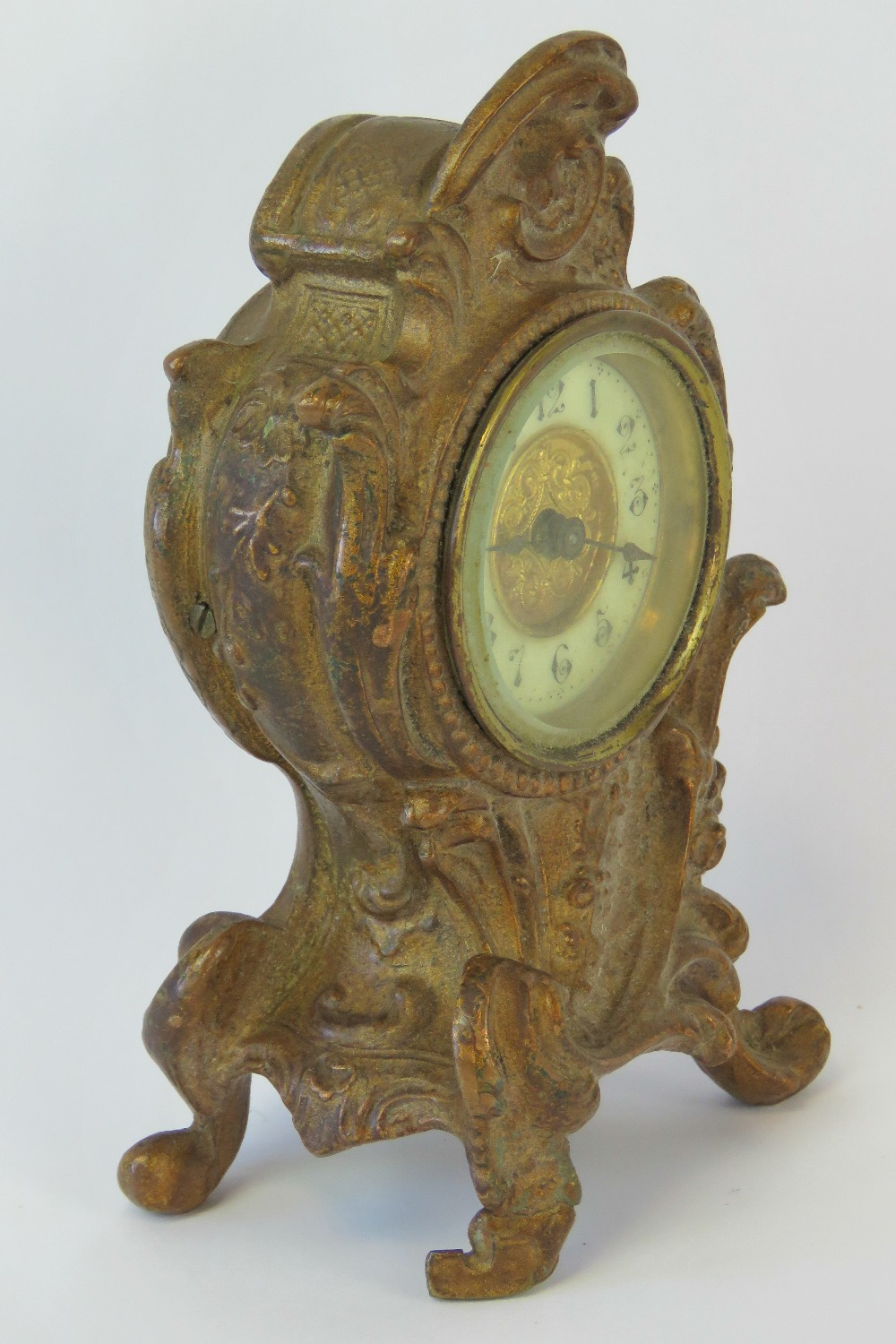 Lot 351 - A small late Victorian boudoir clock of rococo scroll design in a gilt painted white metal case,