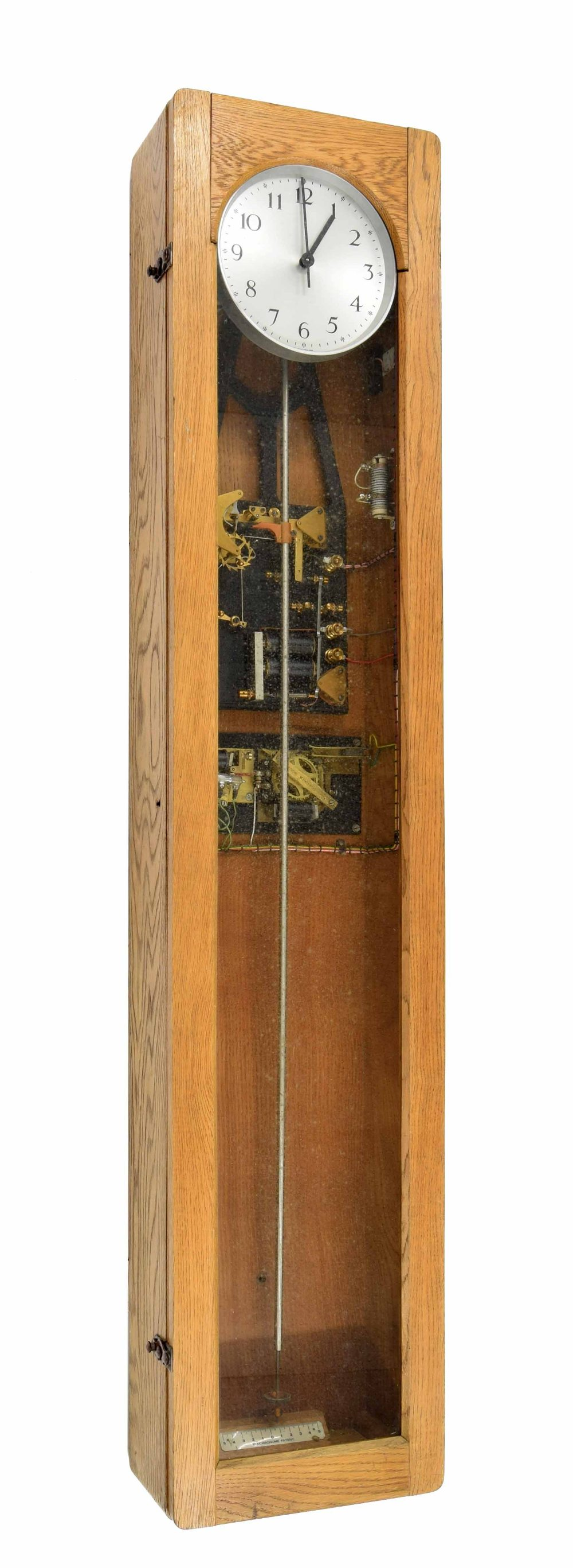 "Lot 1129 - Electric master clock with switch gear, the 6.25"" silvered dial within a light oak glazed case, 49.7"