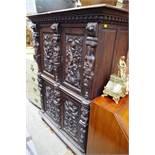 An antique Continental carved oak press cupboard,117cm wide.