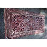 An Eastern rug,with central floral field, having geometric borders, 240 x 115cm.