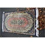 A Chinese blue and pink floral rug,160 x 89cm.