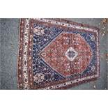 An Eastern rug,having floral and geometric design on a red and blue field, 196 x 138cm.