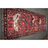 An Eastern rug,having animal motifs on a red field, with floral borders, 320 x 127cm.