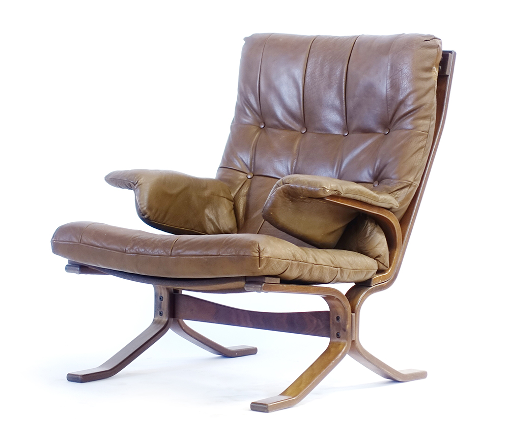 Lot 53 - A 1970's brown button upholstered highback lounge armchair on a laminate bentwood frame,