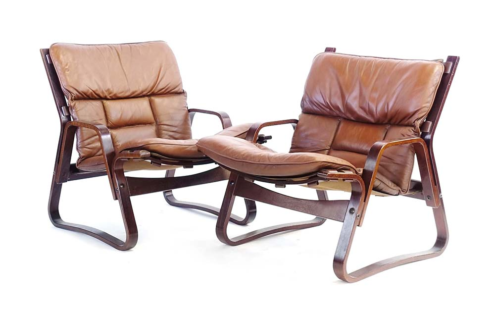 Lot 26 - A pair of brown leather and bentwood lowback lounge armchairs in the manner of Westnofa *See lot 50