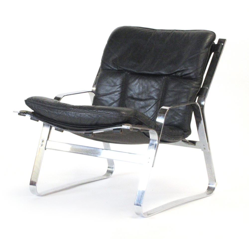 Lot 50 - A 1970's chromed and black leather lowback lounge chair,