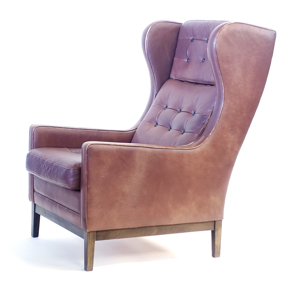 Lot 55 - A 1970's brown button upholstered wingback armchair on stained tapering legs CONDITION
