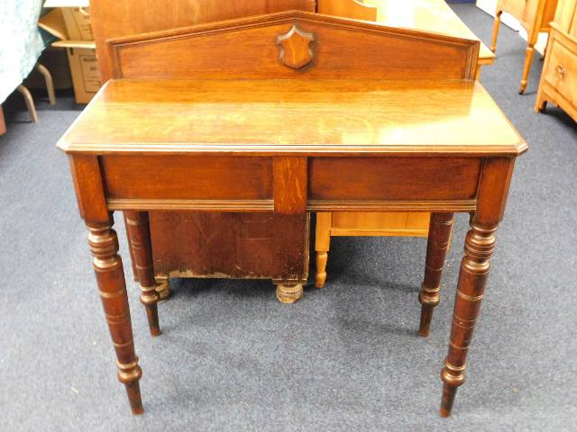 Lot 6 - A oak hall table with shield decor on rear plinth