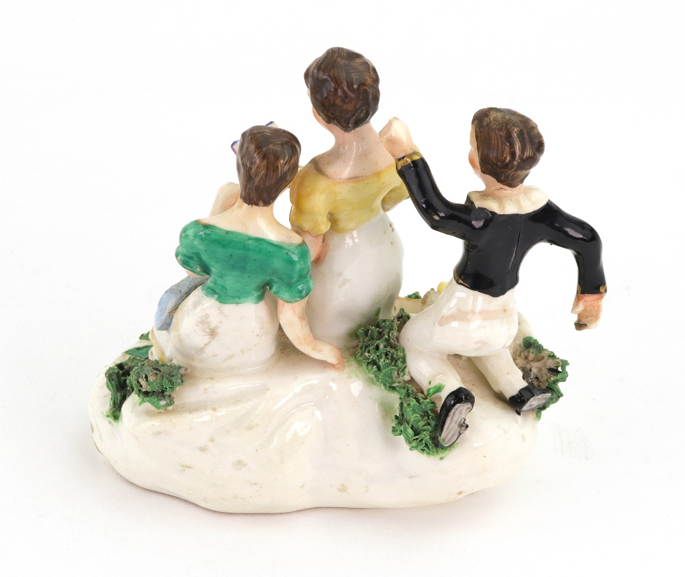 Lot 8 - An English porcelain group, circa 1830, modelled as a mother holding an open book,
