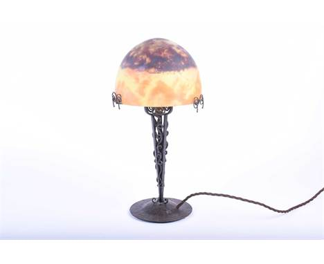 A Secessionist wrought iron table lamp with hand worked metal base, signed Pierre Maynadier, with a frosted glass shade signe